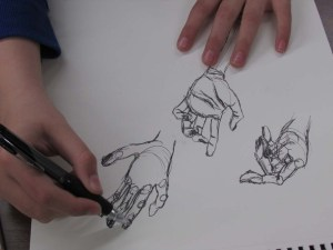 A young art student draws a variety of hand sketches.