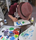 A young beginning painting student starts mixing colors.